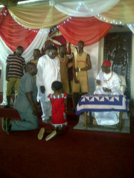 AMARACHI (IN RED) KNEELING BEFORE THE OBA