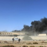Black smoke billows from a warehouse after an airstrike in Zawura