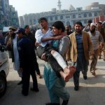 A man carries a student, who was injured during an attack by Taliban gunmen on the Army Public School, after he received treatment at a hospital in Peshawar