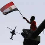 A man waves Egyptian national flag as military helicopter circles over Tahrir Square, after swearing-in ceremony of president elect Sissi, in Cairo