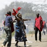 An elderly woman is assisted after riot policemen fired teargas cannisters to disperse protests to oust the Narok county Governor Samuel Tunai in Narok, Kenya