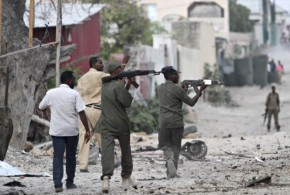 Somali police hold their weapons as they walk outside the Maka Al-Mukarama hotel during an Islamist group al Shabaab attack in the capital Mogadishu
