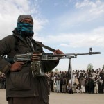 A member of the Taliban insurgent and other people stand at the site during the execution of three men in Ghazni Province