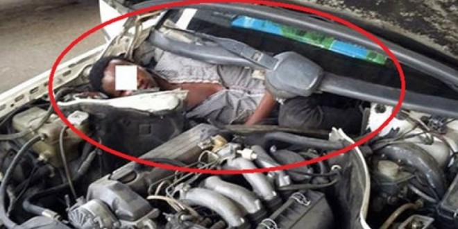 Shocking Photo!!! Desperate African Migrant Caught Hiding In Car Engine To Enter Spain
