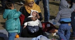 A migrant woman holds a child at a migrant center near the village of Adasevci, Serbia February 12, 2016.      REUTERS/Marko Djurica