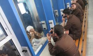 Palestinian men sit in their brown priso