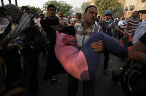 A member of the Muslim Brotherhood and supporter of ousted Egyptian President Mohamed Mursi carries a woman after riot police released tear gas at Kornish El Nile