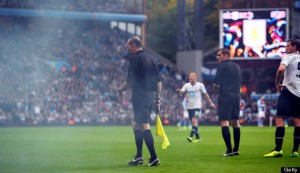 A referee steps onto the field after getting hit by a smoke bomb thrown after Tottenham scored a goal during the English Premier League football match at Villa Park in Birmingham on Oct. 20, 2013.