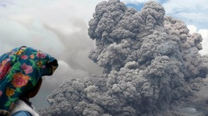 Indonesian villager watches as Mt Sinabung spews hot ash into the air. More than 26,000 people have been forced to flee the volcano.  Picture: AFP