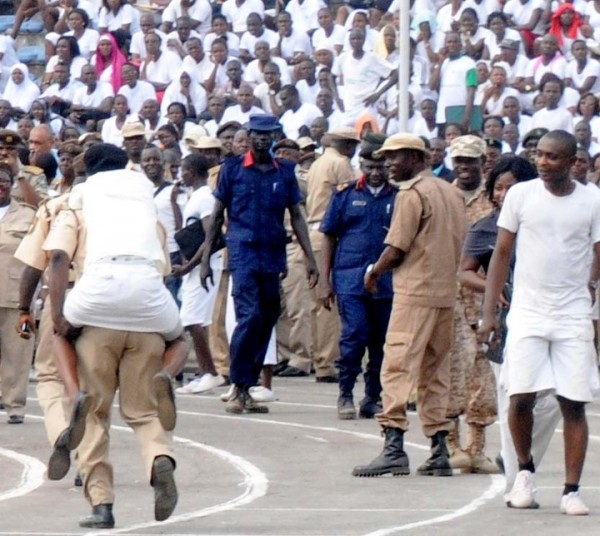 AN OFFICIAL OF THE NIGERIAN IMMIGRATION SERVICE CARRYING ON HIS BACK, A FEMALE APPLICANT WHO FAINTED DURING THE SERVICE'S RECRUITMENT IN IBADAN ON SATURDAY (15/3/14).
