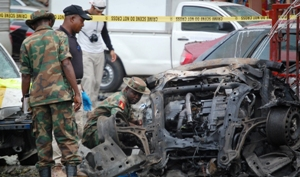 SOLDIERS EXAMINING THE WRECKAGE OF THE ALLEGED BOMBERS' CAR AT EMAB PLAZA, SCENE OF WEDNESDAY'S BLAST IN ABUJA.