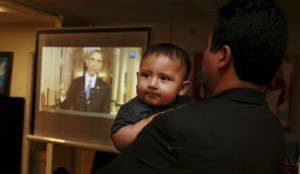 Christian Ramirez holds his nine-month old son Diego while watching President Barack Obama's White House speech on immigration at a viewing party at Alliance San Diego in San Diego