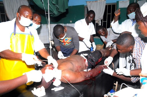 HEALTH WORKERS TAKE CARE OF AN INJURED VICTIM OF JOS BOMB BLAST ON DECEMBER 11, 2014 AT PLATEAU STATE SPECIALIST HOSPITAL, IN JOS. AFP PHOTO/STRINGER