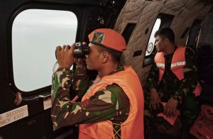 Indonesian Air Force Super Puma helicopter of 6th Air Squadron uses a binocular to scan the horizon during a search operation for the victims of AirAsia
