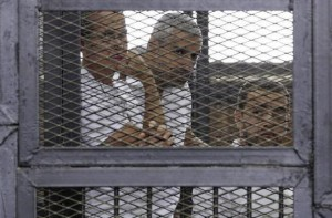 Al Jazeera journalists Greste, Fahmy and Mohamed stand behind bars at a court in Cairo