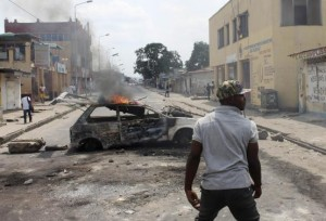 A demonstrator walks near a car set ablaze to barricade a street during a protest in the Democratic Republic of Congo's capital Kinshasa