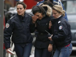 Police take charge of a woman at the scene of a shooting in the street of Montrouge near Paris