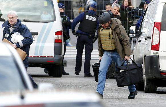 Belgian police investigators arrive outside an apartment in central Verviers