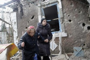 People walk outside a house, which according to locals was recently damaged by shelling, in Donetsk