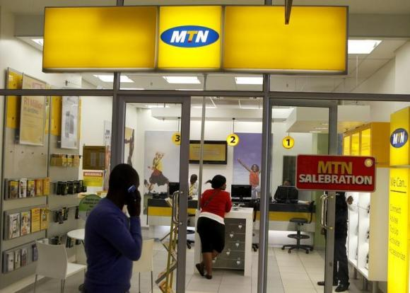 Man speaks on a mobile phone as he walks past a MTN shop at a shopping mall south of Johannesburg