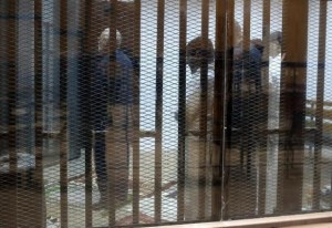 Muslim Brotherhood's Supreme Guide Mohamed Badie prays behind bars with other Muslim Brotherhood members at a court in the outskirts of Cairo