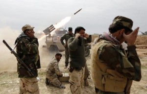 Shi'ite fighters cover their ears as a rocket is launched during a clash with Islamic State militants in the town of al-Alam