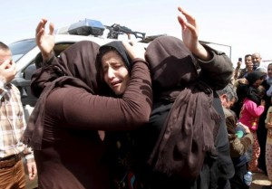 Members of the minority Yazidi sect hug each other on the outskirts of Kirkuk