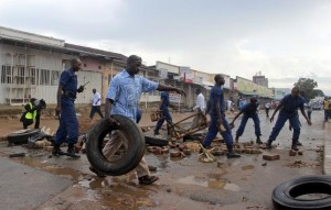 Burundi policemen clear a barricade set up by protestors opposing President Pierre Nkurunziza from running for a third term, in Bujumbura