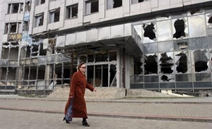 A woman walks past a building damaged by fighting in Donetsk