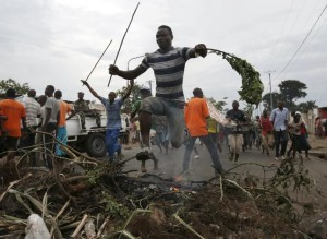 A protester jumps over a barricade during a protest against Burundi President Pierre Nkurunziza and his bid for a third term in Bujumbura, May 18, 2015.  REUTERS/Goran Tomasevic