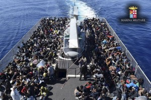 Migrants sit in Italian navy ship Vega during a rescue operation off the coast of Sicily, in this handout picture courtesy of the Italian Marina Militare (Marine Military) released on May 4, 2015. REUTERS/Marina Militare/Handout via Reuters