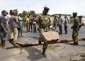 A soldier drops a stone while removing a barricade which was set up by protesters in Bujumbura, Burundi May 16, 2015. REUTERS/Goran Tomasevic