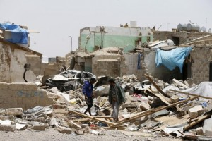 People walk at the site of a Saudi-led air strike that hit a residential area last month near Sanaa airport, May 18, 2015. REUTERS/Khaled Abdullah