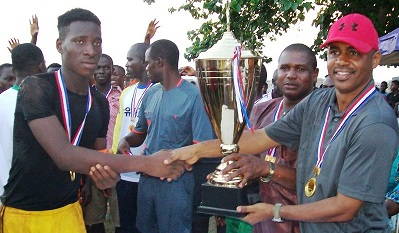 THE COMMANDER, ONITSHA MILITARY CANTONMENT, COL. MOHAMMED BELLO PRESENTING A TROPHY TO THE CAPTAIN OF BARCA FC, BARRACKS, MASTER CHIGOZIE ONYEKACHI DURING THE COMMANDERS CUP, FINALS, MALE FOOTBALL COMPETITION