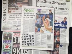 A combo taken on Wednesday June 17, 2015 showing some of the British national newspapers of Tuesday June 16 and featuring at centre the back page of The Times showing it's daily crossword puzzle. A crossword-loving British lawyer hid a marriage proposal in Tuesday's edition of The Times newspaper's daily puzzle. Matthew Dick thought of the cryptic way of popping the question to girlfriend Delyth Hughes, and persuaded the newspaper to agree. (AP Photo/Tony Hicks)