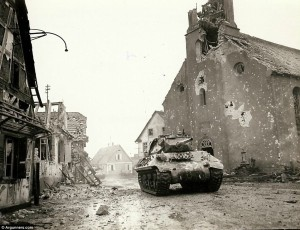 On patrol: An American tank is seen driving down a battle-ravaged street in Rohrwiller, France, on February 4, 1945