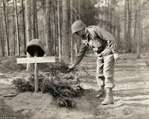Forest burial: An American soldier decorates the grave of an unknown U.S. soldier, who was buried by the enemy before retreating