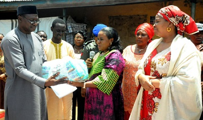 WIFE OF THE GOVERNOR OF PLATEAU, MRS REGINA LALONG (M), PRESENTING RELIEF MATERIALS TO THE COORDINATOR OF STEFANOS FOUNDATION'S INTERNALLY DISPLACED PERSONS (IDPs) CAMP, MR MARK LIPDO (L), DURING OFFICIAL PRESENTATION OF RELIEF MATERIALS TO IDPs TO MARK PRESIDENT MUHAMMADU BUHARI'S FIRST 100 DAYS IN OFFICE, IN JOS ON FRIDAY (4/9/15). RIGHT IS MRS MAIRO AL-MAKURA WHO REPRESENTED MRS AISHA BUHARI AT THE OCCASION. 6416/4/9/2015/SAA/BJO/NAN
