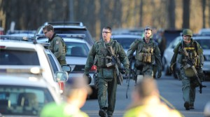 State Police inspect the area at the aftermath of  a school shooting at a Connecticut elementary school  that brought police swarming into the leafy neighborhood. (Don Emmert/Getty Images)