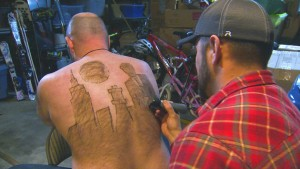 CORRECTS DATE TO DEC. 29 FROM DEC. 30 - In this Dec. 29, 2015 photo provided by KTVB-TV, Tyler Harding, right, trims a design on Mike Wolfe out of his back hair in Nampa, Idaho. Wolfe and Harding meet up several times throughout the year to design a new creation on Wolfe's back. The designs have since been compiled for a calendar. (Mike di Donato/KTVB via AP) TV OUT, MANDATORY CREDIT