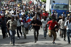 Demonstrators run during a protest in Port-au-Prince, on January 22, 2016. Demonstrators marched to protest against the presidential elections. Haiti's electoral authority has postponed Sunday's planned presidential run-off amid mounting opposition street protests and voting fraud allegations. The second round of presidential elections was scheduled for January 24 between ruling party candidate Jovenel Moise and Jude Celestin but was suspended by CEP. / AFP / HECTOR RETAMAL (Photo credit should read HECTOR RETAMAL/AFP/Getty Images)