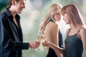 Young couple holding glasses with champagne and woman looking for them, outdoors, focus on woman with red hair and man