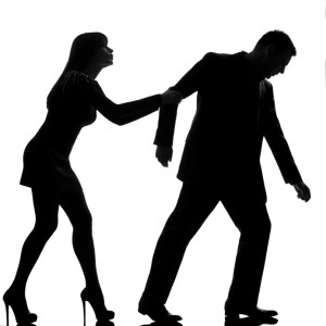 one caucasian couple dispute separation man leaving and woman holding back in studio silhouette isolated on white background