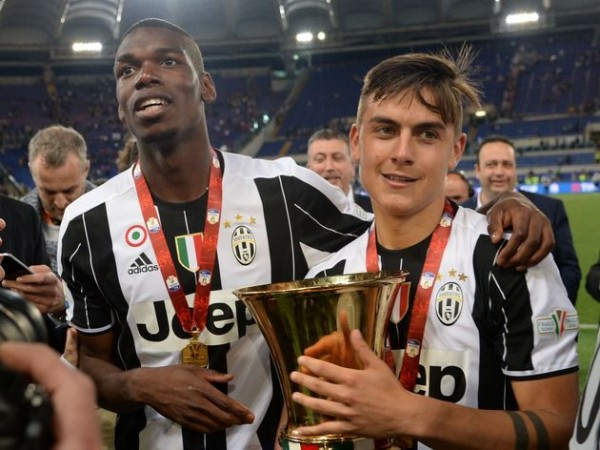 Juventus' forward from Argentina Paulo Dybala (R) and Juventus' midfielder from France Paul Pogba celebrate with the trophy after winning the Italian Tim Cup final football match AC Milan vs Juventus on May 21, 2016 at the Olympic Stadium in Rome. Juventus won 0-1 in the extra time. AFP PHOTO / FILIPPO MONTEFORTE / AFP / FILIPPO MONTEFORTE (Photo credit should read FILIPPO MONTEFORTE/AFP/Getty Images)