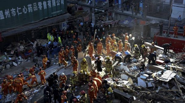 Rescuers search for victims on the site of collapsed residential buildings in Wenzhou city in east China's Zhejiang province, Monday Oct. 10, 2016. More than dozen people were believed to be buried after four residential houses collapsed on Monday early morning. (AP Photo)
