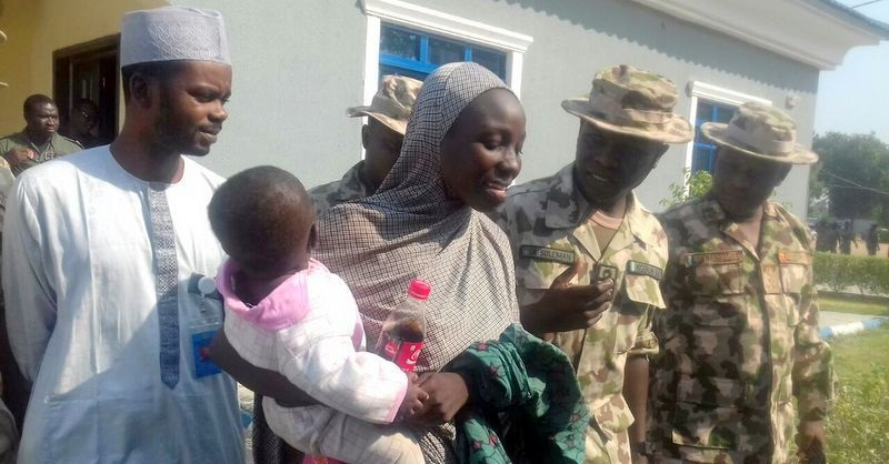 Rescued Chibok girl Maryam Ali Maiyanga and her 8-month-old baby with Nigerian military officials in Borno state