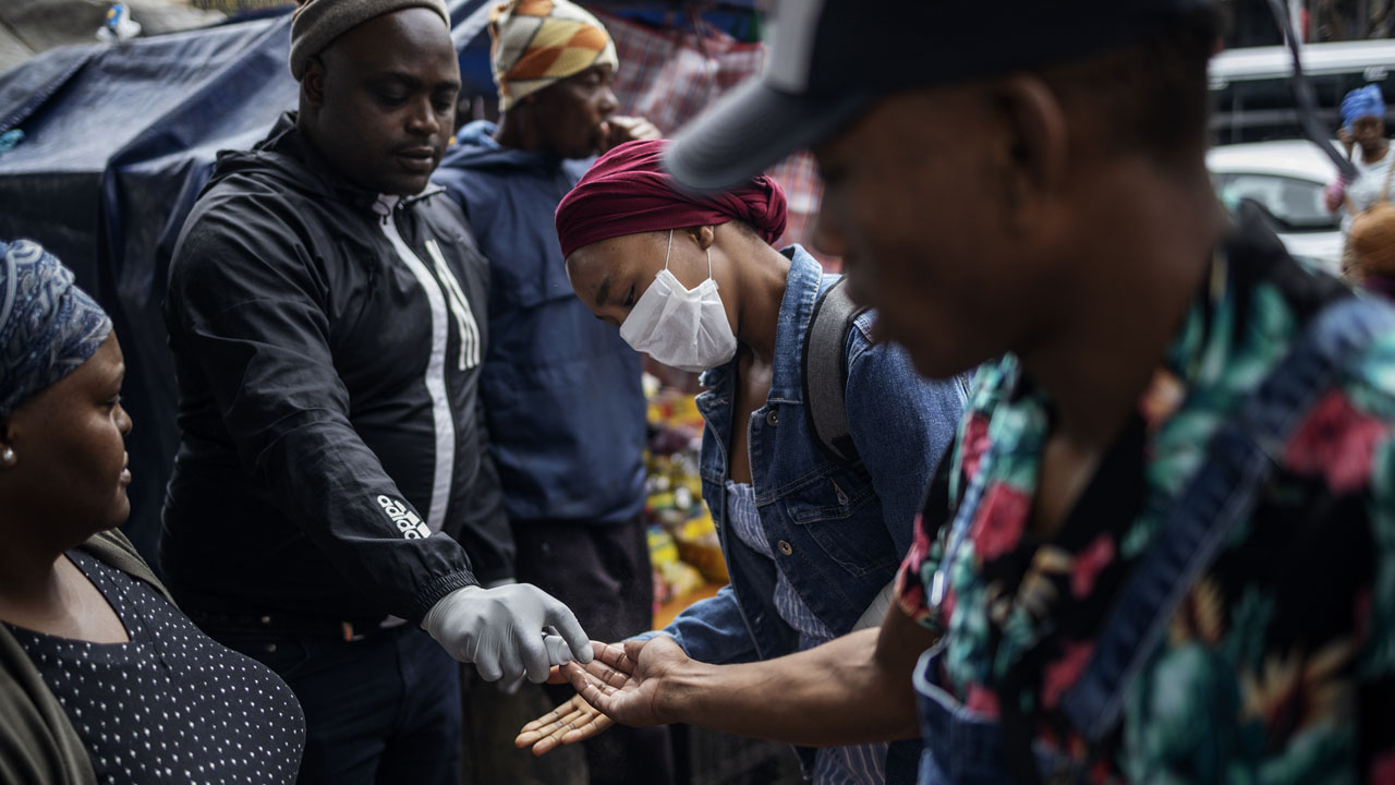 A man sprays commuters with hand sanitiser in South Africa