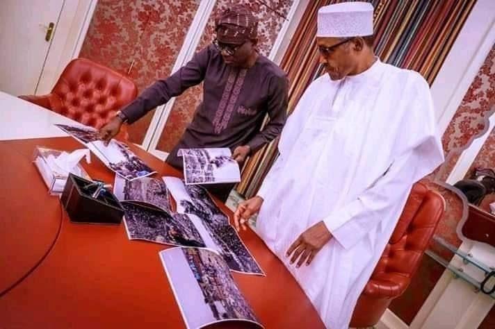 Photo of Sanwo-Olu showing president Buhari photos of Lagos explosion