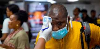 A passenger's body temperature is being tested at the gate of entry upon arrival at the Murtala International Airport in Lagos, on March 2, 2020. -