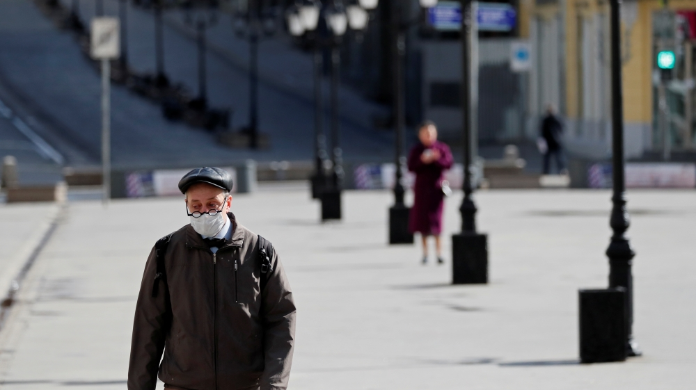 A man wearing a protective face mask walks along the street in Moscow, Russia [Shamil Zhumatov/Reuters]